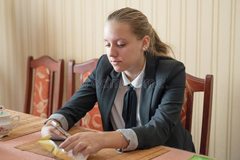Adolescente en uniforme escolar con el teléfono fotos de archivo