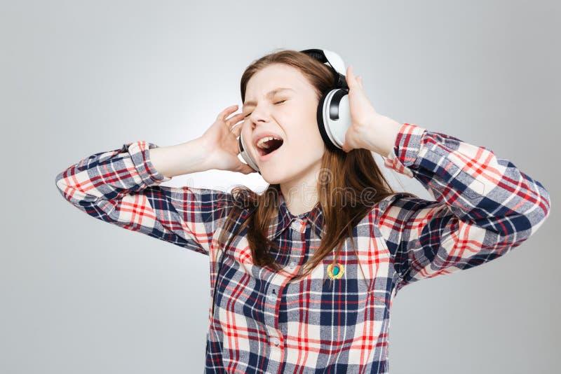 Adolescente encantador que escucha la música y que canta imagenes de archivo