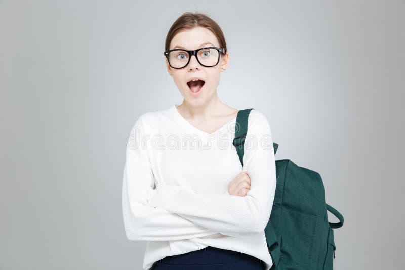 Adolescente encantador surpreendido nos vidros que estão com boca aberta foto de stock