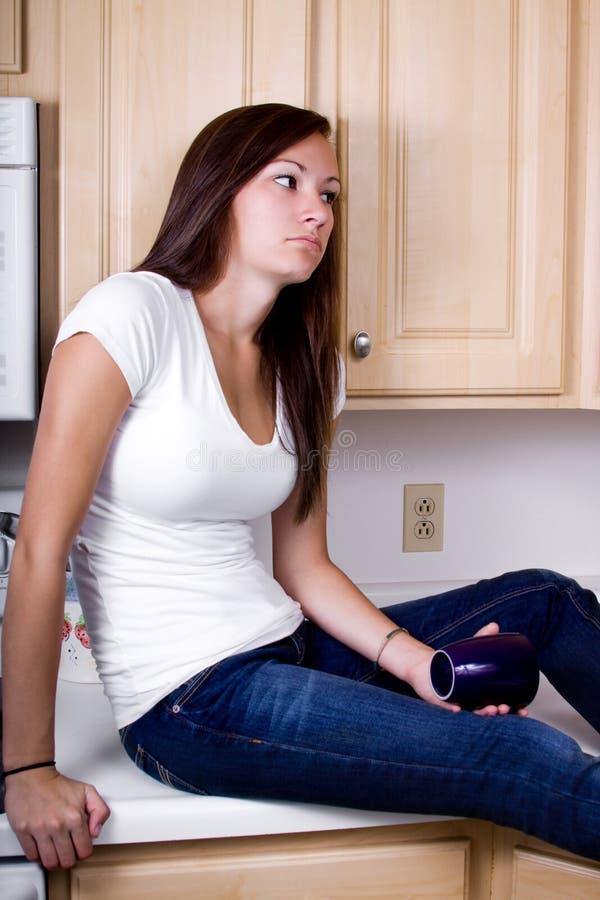 Adolescente ennuyée dans la cuisine photo stock