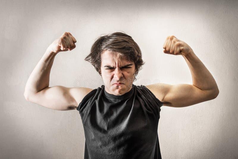 Adolescente enojado que muestra los músculos imagen de archivo