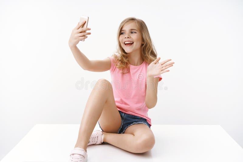 Adolescente enthousiaste et enthousiaste jeune fille blonde heureuse assise les jambes croisées sur le sol, tenir un smartphone,  photo libre de droits