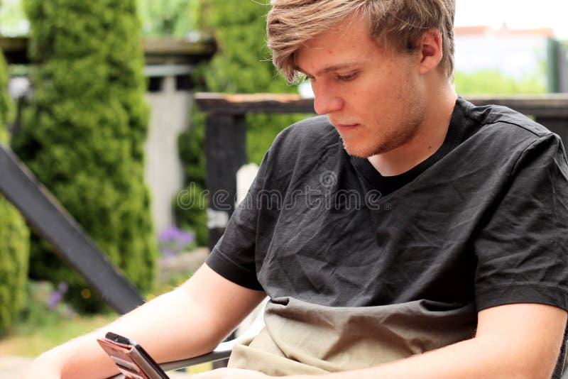 Adolescente entretenido por su smartphone imágenes de archivo libres de regalías