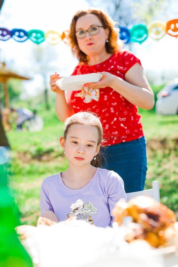 Adolescente envelheceu tristemente a menina que senta-se pela tabela no partido de jardim do aniversário imagem de stock
