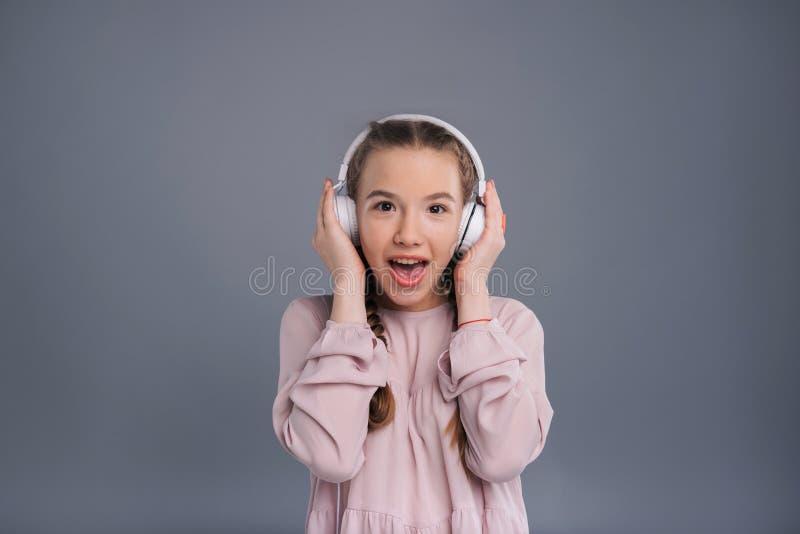 Adolescente estatico che ascolta la musica in cuffie immagine stock libera da diritti