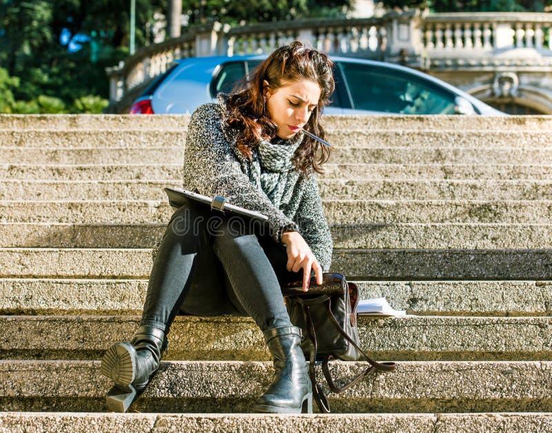 Adolescente/estudante novo que procura em seu saco fotografia de stock royalty free