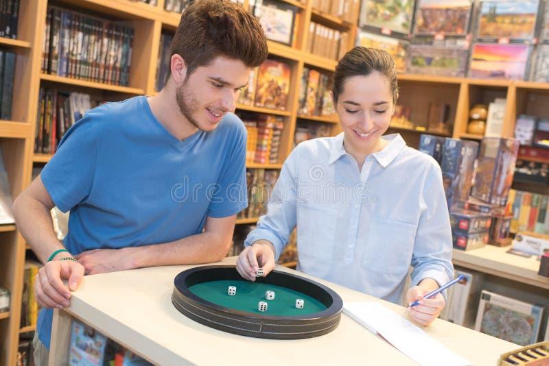 Adolescente et ami jouant des matrices dans le magasin de jouet image stock