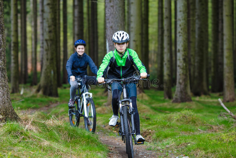 Adolescente et garçon faisant du vélo sur des traînées de forêt photo stock