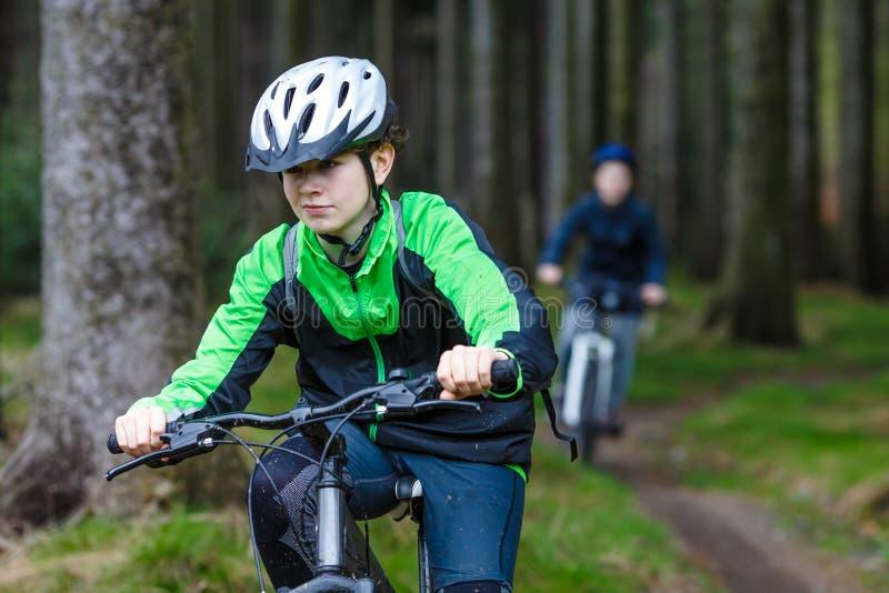 Adolescente et garçon faisant du vélo sur des traînées de forêt image libre de droits
