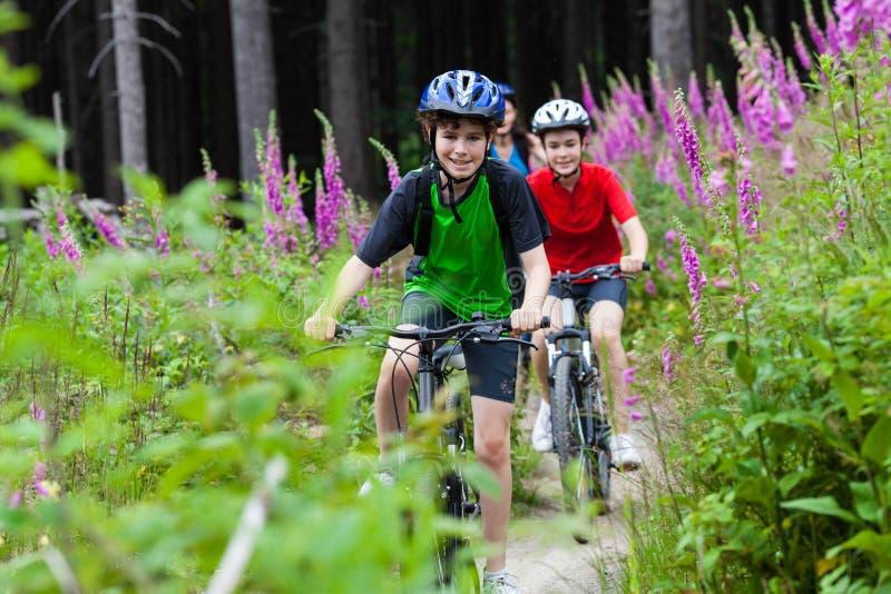 Adolescente et garçon faisant du vélo sur des traînées de forêt image stock
