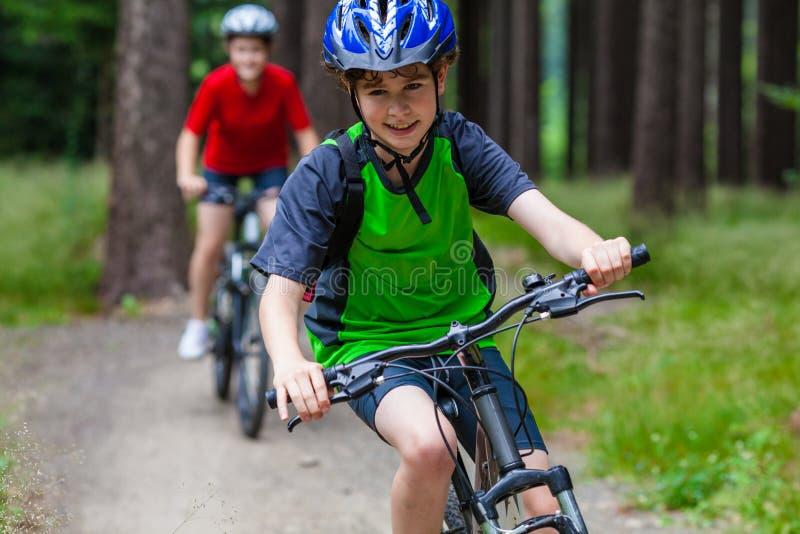 Adolescente et garçon faisant du vélo sur des traînées de forêt photos libres de droits