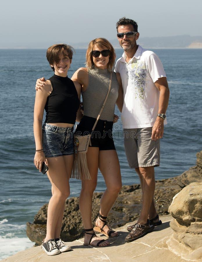 Adolescente et ses parents d'une cinquantaine d'années se tenant prêt l'océan images stock