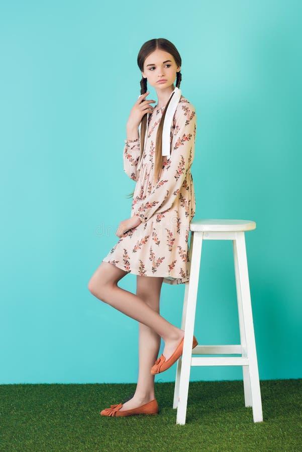 adolescente fêmea no vestido na moda do verão com as tranças que levantam perto do tamborete foto de stock