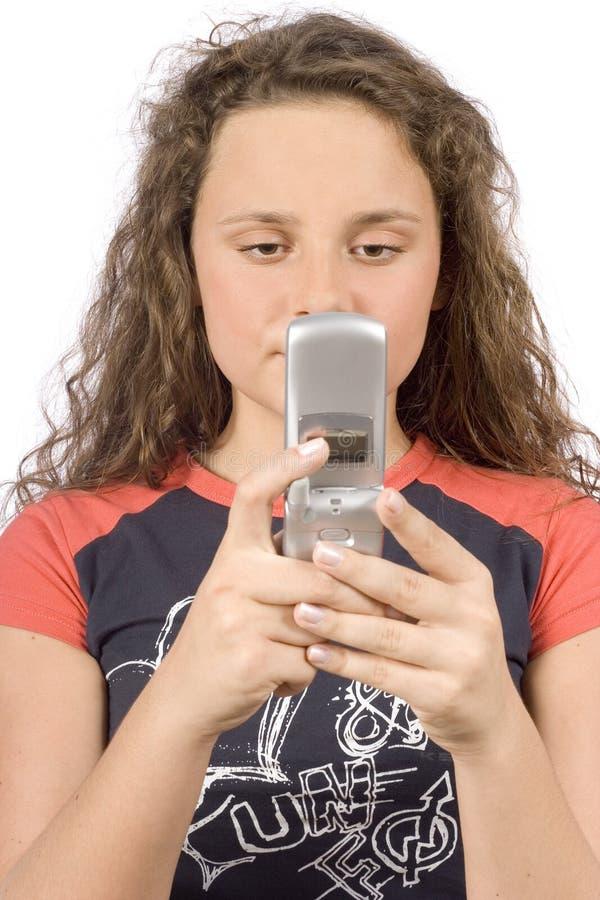 Adolescente fêmea que escreve a mensagem de texto curta imagem de stock