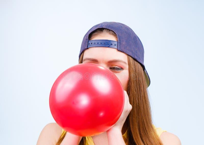 Adolescente fêmea que infla o balão vermelho imagens de stock royalty free