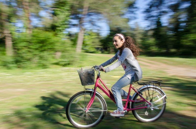 Adolescente faisant du vélo sur des traînées de forêt photo stock