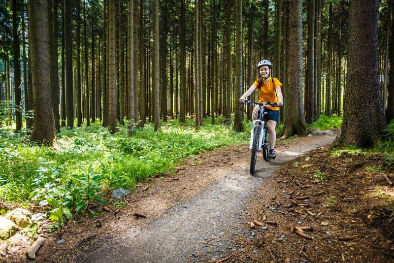 Adolescente faisant du vélo sur des traînées de forêt image libre de droits