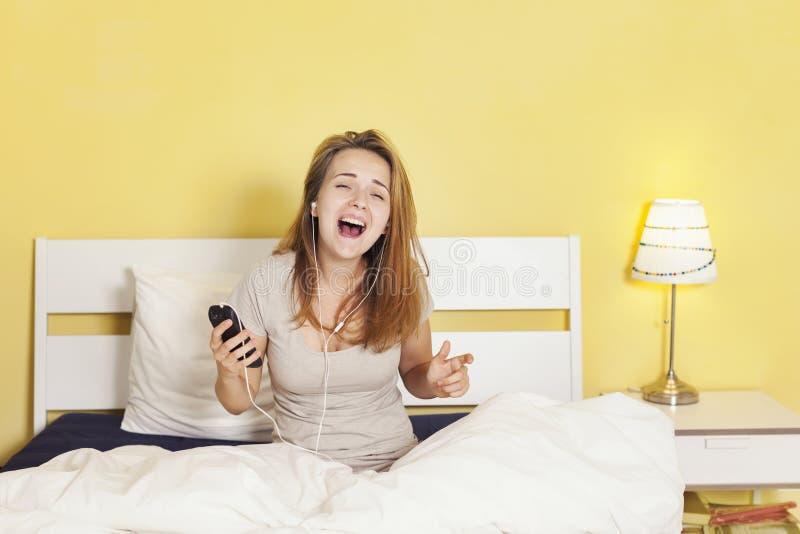 Adolescente felice in cuffie che ascolta la musica da astuto fotografie stock libere da diritti