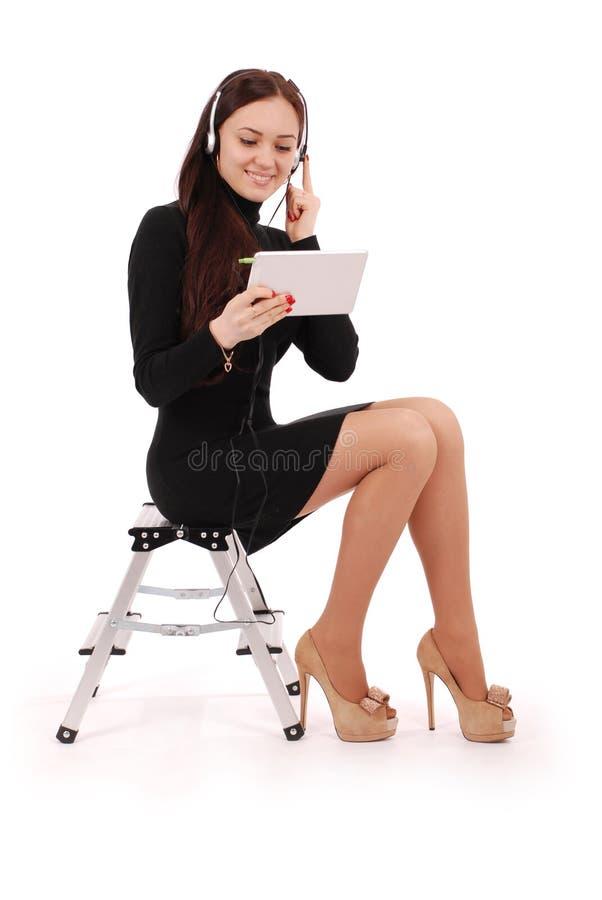 Adolescente felice dello studente che si siede sulla scala che esamina tabl fotografia stock