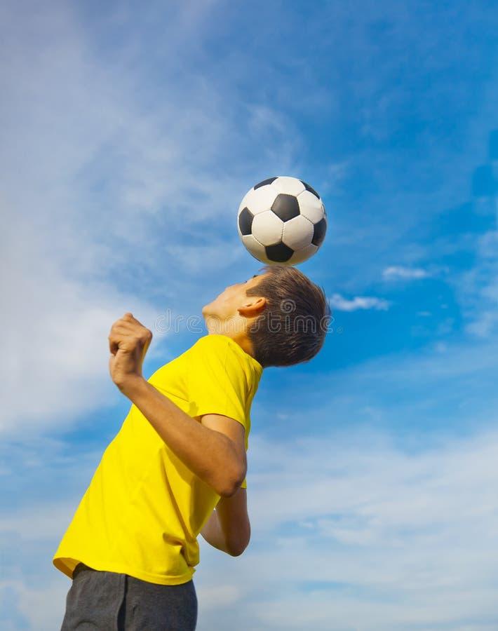 Adolescente feliz con un balón de fútbol en su cabeza en el CCB del cielo azul fotografía de archivo