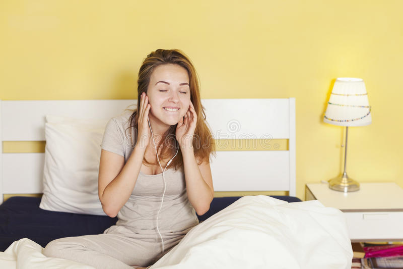 Adolescente feliz en auriculares que escucha la música de elegante imagen de archivo
