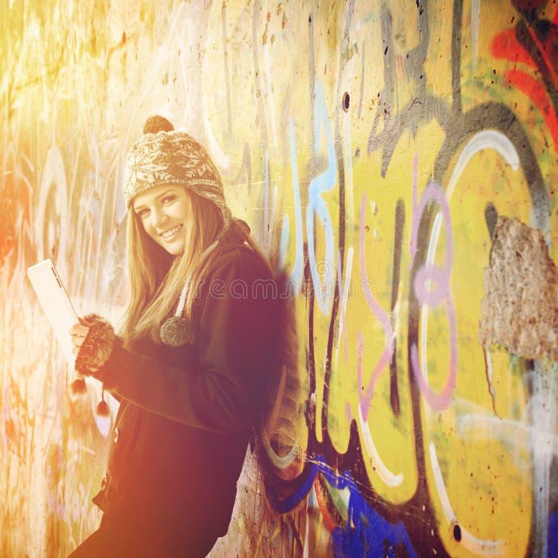 Adolescente feliz lindo con la tableta al aire libre imagen de archivo