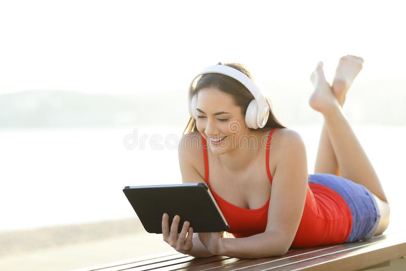 Adolescente feliz mira y escucha los vídeos en la tableta imagen de archivo