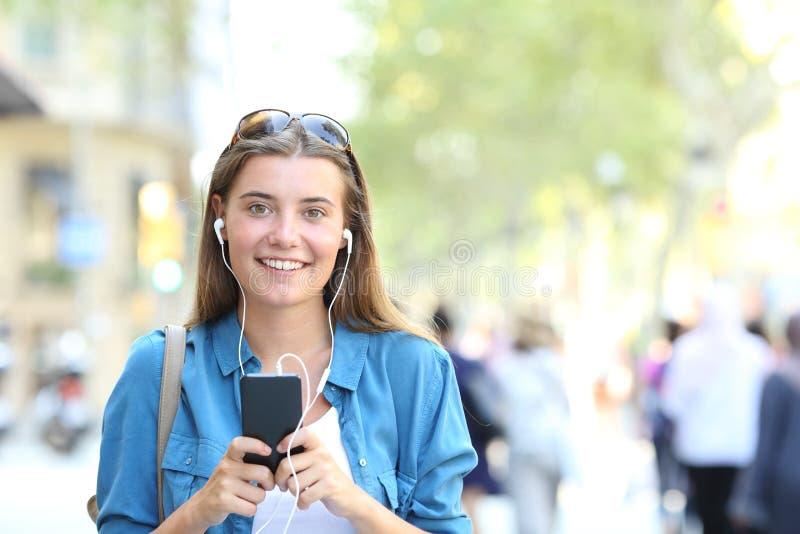 Adolescente feliz olha a câmera que escuta a música imagens de stock