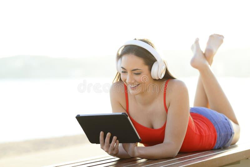 Adolescente feliz olha e escuta vídeos na tabuleta imagem de stock