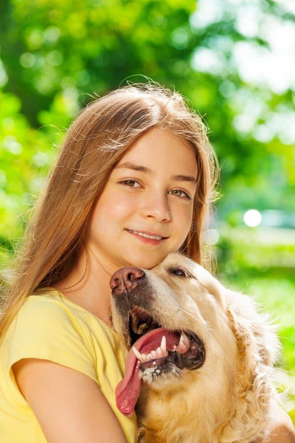 Adolescente feliz que abraça o cão fora do retrato fotografia de stock royalty free