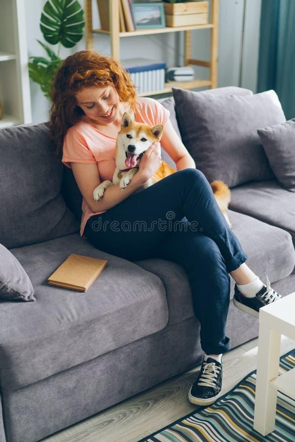 Adolescente feliz que abraça o cão que senta-se no sofá no sorriso moderno do apartamento imagens de stock royalty free