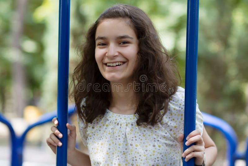 Adolescente feliz que balança no parque imagens de stock