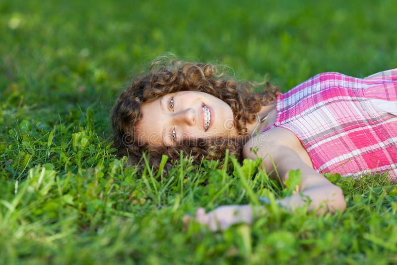 Adolescente feliz que encontra-se na grama fotos de stock royalty free