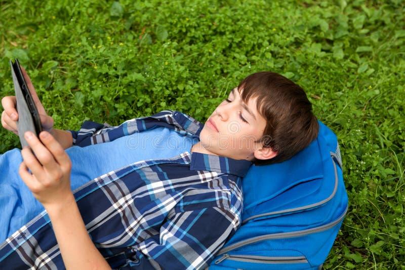 Adolescente feliz que encontra-se na grama no parque imagem de stock