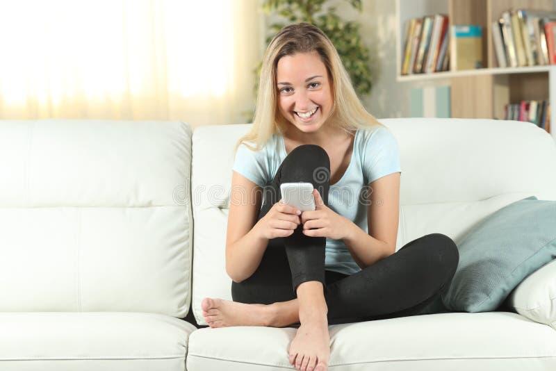 Adolescente feliz que guarda o telefone esperto que olha o imagem de stock