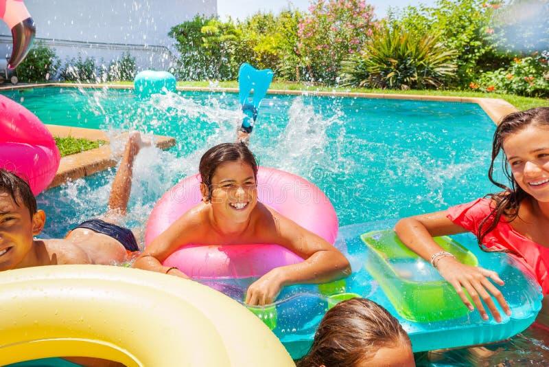 Adolescente feliz que juega a juegos de la piscina con los amigos imagen de archivo