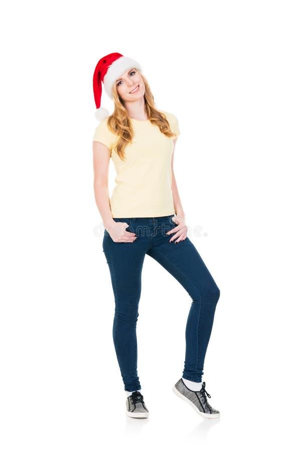 Adolescente feliz que levanta em um chapéu do Natal no branco fotografia de stock royalty free