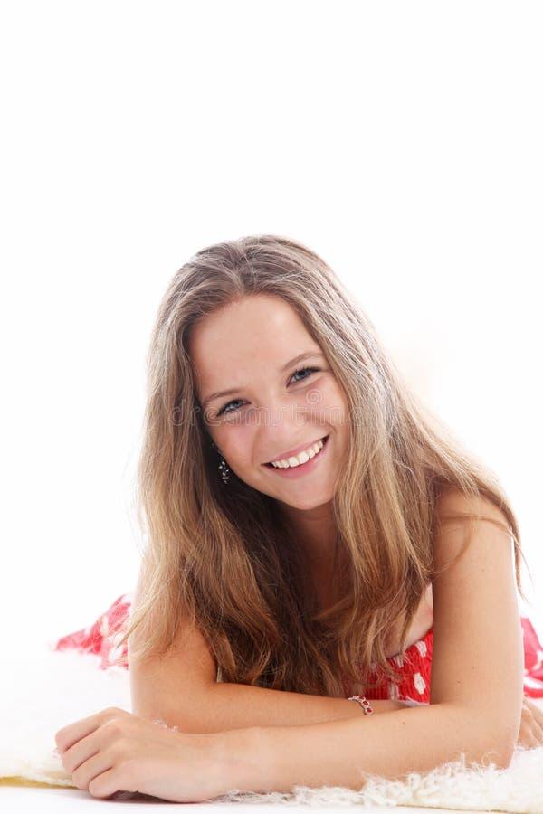 Adolescente feliz que relaxa em um tapete fotos de stock