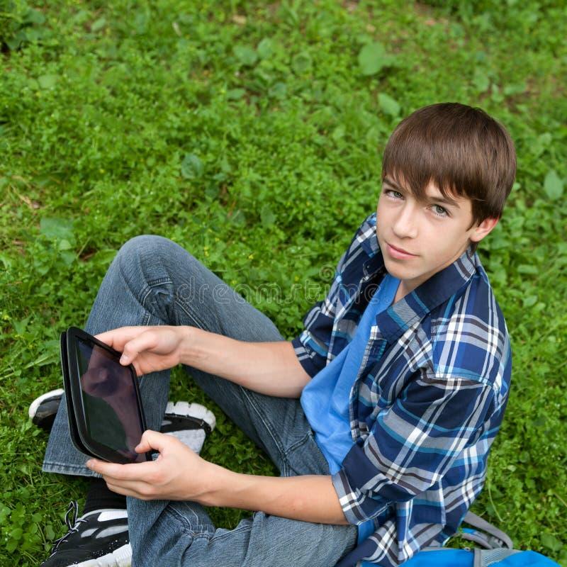 Adolescente feliz que senta-se na grama no parque imagem de stock royalty free