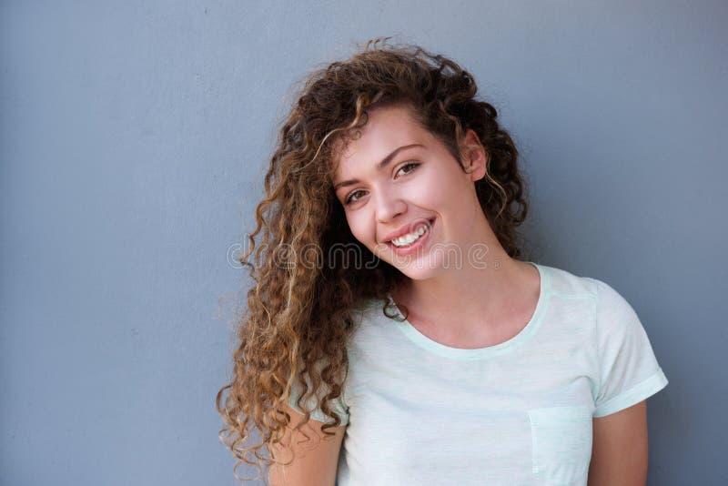 Adolescente feliz que sorri contra a parede cinzenta imagem de stock royalty free