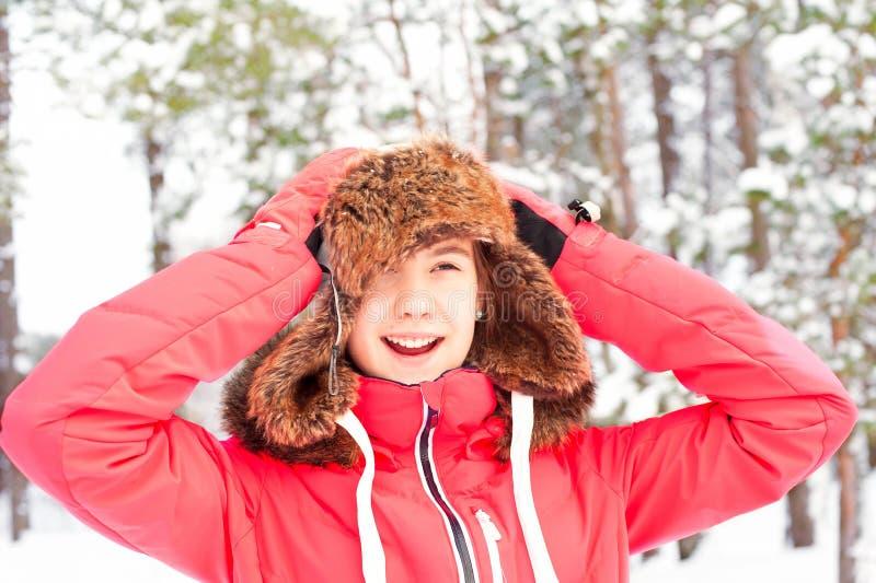 Adolescente feliz sonriente en el earflap caliente que se divierte en invierno fotografía de archivo