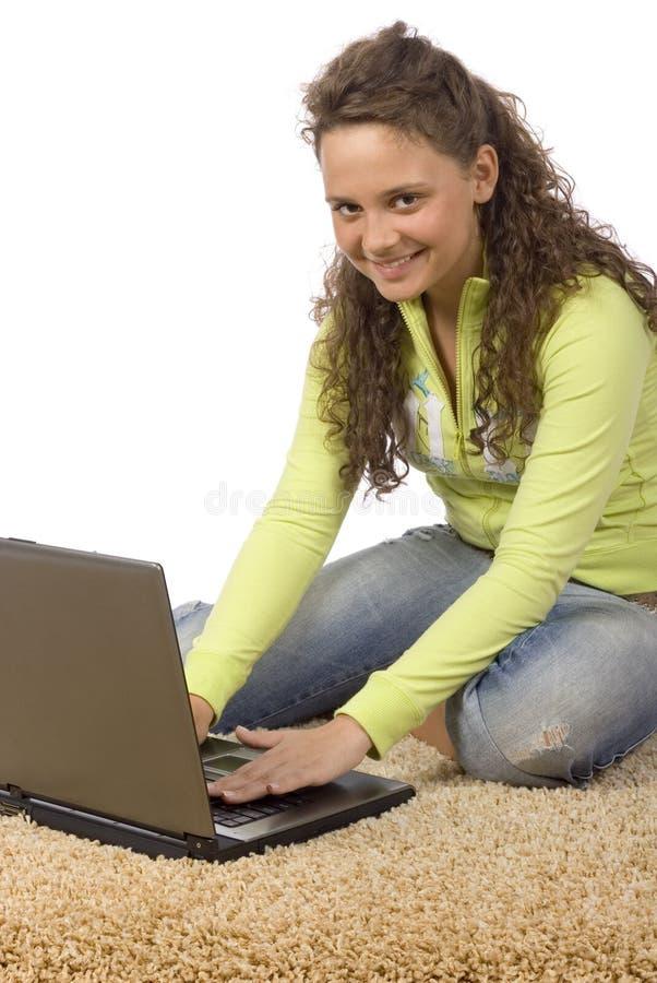 Adolescente femenino en la alfombra con la computadora portátil imagen de archivo libre de regalías