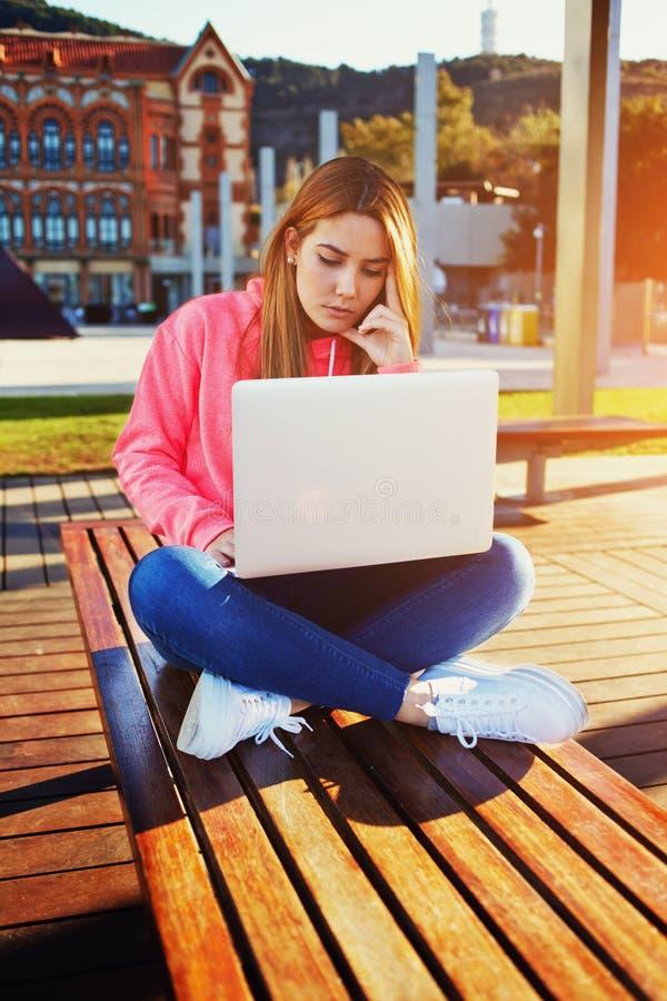 Adolescente femenino encantador que se sienta en banco de parque con el ordenador portátil foto de archivo