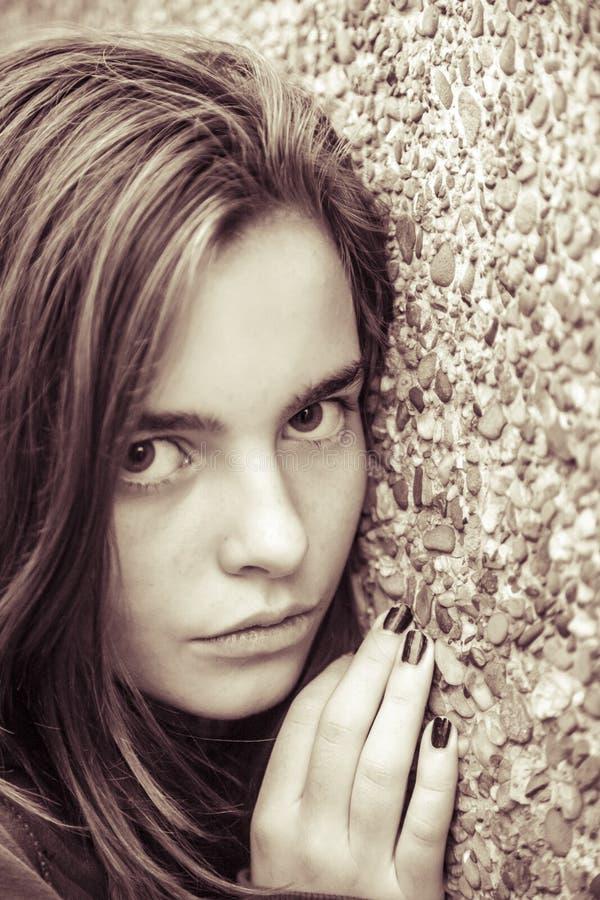 Adolescente femenino que inclina aquí la cara en una pared foto de archivo libre de regalías