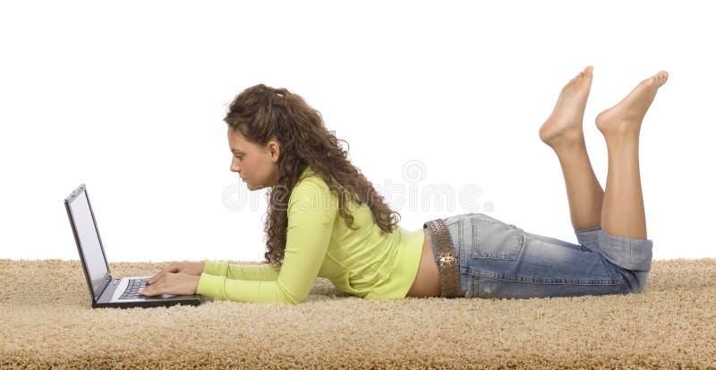 Adolescente femenino que miente en la alfombra con la computadora portátil foto de archivo