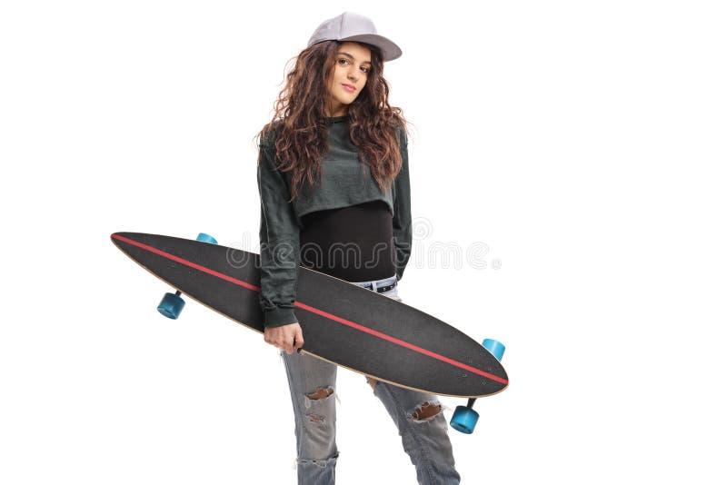 Adolescente femenino que presenta con un longboard imagenes de archivo