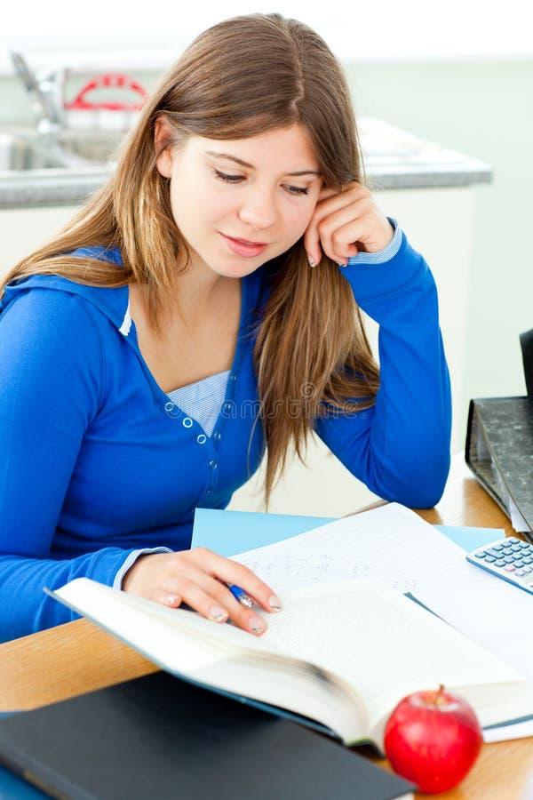 Adolescente femminile allegro che studia nella cucina immagini stock