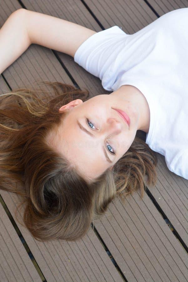 Adolescente femminile che sorride, layingon il pavimento Estate, ritratto della ragazza con capelli lunghi e biondi fotografia stock