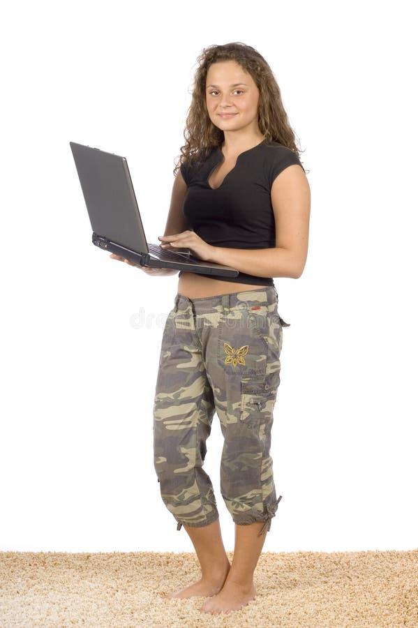 Adolescente femminile che sta sul tappeto con il computer portatile fotografie stock libere da diritti