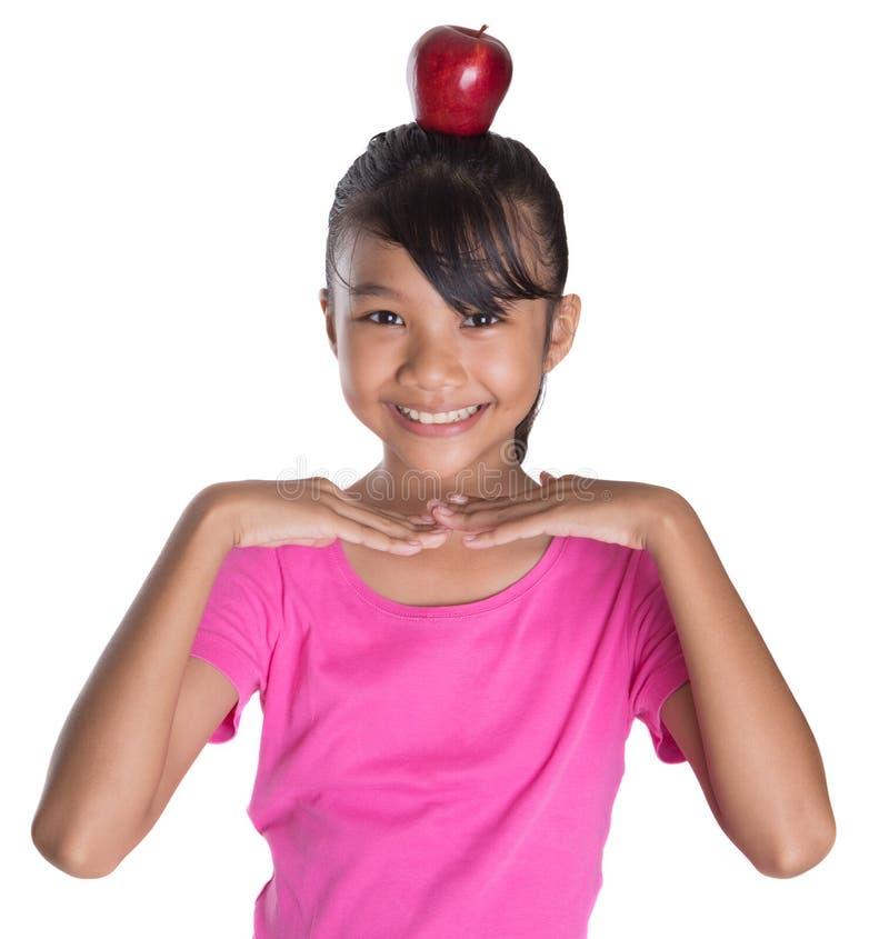 Adolescente femminile con Apple sul suo II capo immagini stock libere da diritti